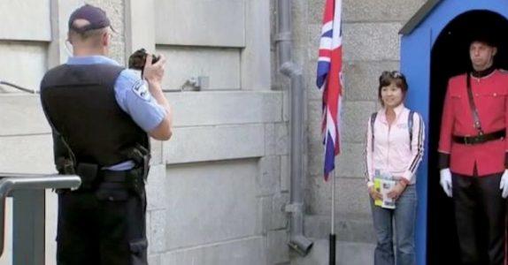 Turisten poserer foran den alvorlige vakten. Når hun ser bildet, klarer hun ikke å holde latteren tilbake!